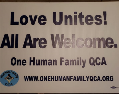 Picture of a yard sign that reads 'Love United! All Are Welcome. One Human Family QCA,' with the OHF QCA logo and the URL to their website.